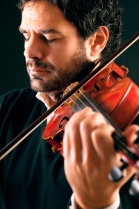 Violinist playing in black background.